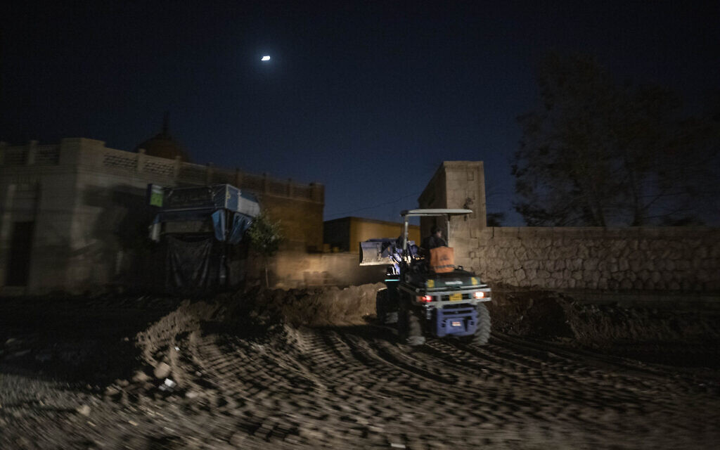 A bulldozer knocks down walls and tombs amid work to clear way for a new highway running through the historic Northern Cemetery in Cairo, Egypt, Sunday, July 26, 2020. (AP Photo/Nariman El-Mofty)
