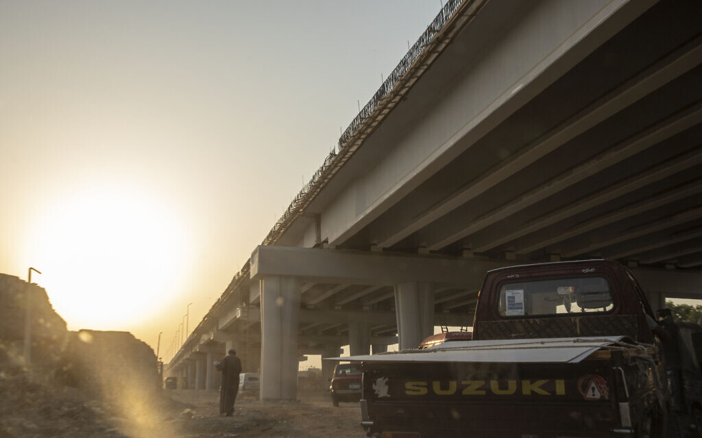 A man walks under a new highway flyover under construction through the Southern Cemetery, part of the City of the Dead, a UNESCO World Heritage Site, in Cairo, Egypt, Tuesday, July 28, 2020. (AP Photo/Nariman El-Mofty)