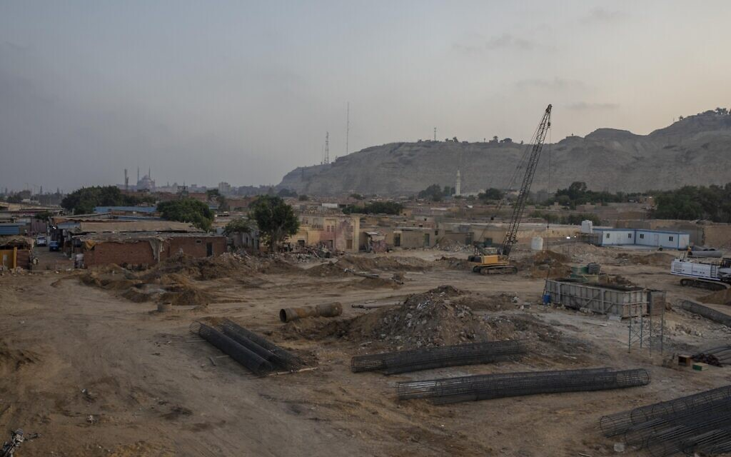 Construction work continues on a highway flyover in a portion cleared of graves in the City of Dead in Cairo, Egypt, with the Citadel, a medieval fortress, visible in the distance Wednesday, July 29, 2020. (AP Photo/Nariman El-Mofty)