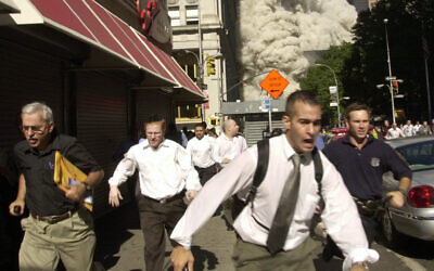 In this September 11, 2001, photo, people, including Stephen Cooper on the far left, run from the collapse of one of the twin towers at the World Trade Center in New York. (AP Photo/Suzanne Plunkett)