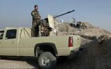 Illustrative photo: A militiaman of the Kurdistan Freedom Party, an Iranian Kurdish opposition group, stands behind his truck-mounted machine gun near the Iraqi city of Kirkuk on September 5, 2016. (AP/Balint Szlanko)