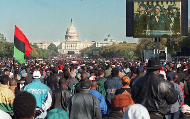 In this Oct. 16, 1995 file photo, a video screen shows Nation of Islam leader Louis Farrakhan speaking during the Million Man March at the Mall in Washington. The Capitol is seen in the background. Two decades later, the march Farrakhan organized, which drew hundreds of thousands to Washington, remains a cultural touchstone. (AP Photo/Steve Helber)