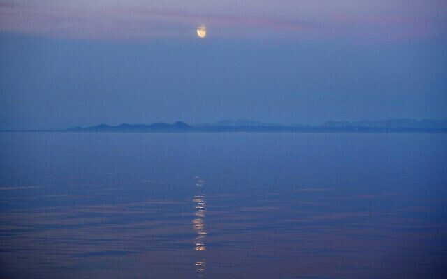 The moon rises over the coast of Alaska as the Finnish icebreaker MSV Nordica sails along the international date line through the Bering Strait, July 14, 2017. (AP Photo/David Goldman)