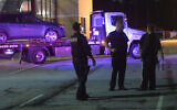 Illustrative: Law enforcement officers talk as a car is towed away in the Mt. Zion High School parking lot as part of an investigation into a shooting on May 18, 2018, near Atlanta, Georgia. (AP/John Amis)