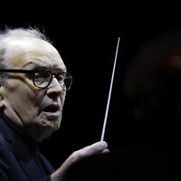 "In this March 6, 2018, photo, Italian composer Ennio Morricone directs an ensemble during a concert of his ""60 Year Of Music World Tour"" in Milan, Italy. (AP Photo/Luca Bruno)"