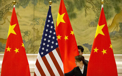 Chinese staffers adjust US and Chinese flags before the opening session of trade negotiations between US and Chinese trade representatives at the Diaoyutai State Guesthouse in Beijing on February 14, 2019. (AP Photo/Mark Schiefelbein, Pool)