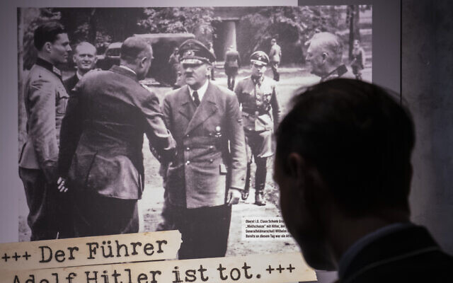 Visitors stands in front of a poster during a press preview of the special exhibition 'The Fuehrer Adolf Hitler is dead - Attempted Assassination and coup d'etat on 20 July 1944.' by the Bundeswehr Museum of Military History in Dresden, Germany, Wednesday, July 3, 2019.  (AP Photo/Jens Meyer)
