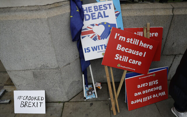 Placards belonging to remain in the European Union, anti-Brexit protesters stand outside the Houses of Parliament in London, January 7, 2020. (Matt Dunham/AP)
