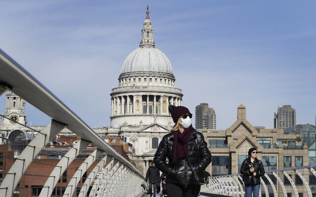 People wear masks as they walk in London over the River Thames on Millennium Bridge near St Paul's Cathedral, seen in the background, March 22, 2020. (AP Photo/Kirsty Wigglesworth)