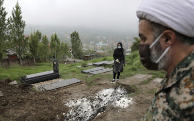 A woman wearing mask and gloves prays at the grave of her mother, who died from the novel coronavirus, at a cemetery in the outskirts of the city of Babol, in north of Iran on April 30, 2020. (AP Photo/Ebrahim Noroozi)