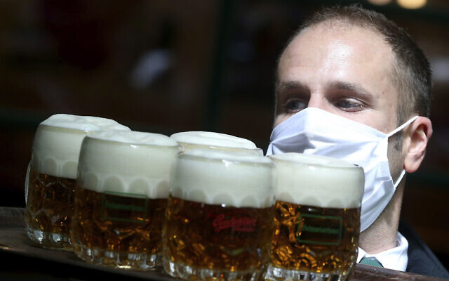 Illustrative: A waiter wears a face mask as he carries beer through a restaurant in Vienna, Austria, May 14, 2020. (AP Photo/Ronald Zak)