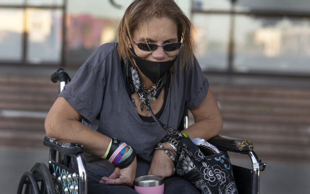 In this Thursday, May 14, 2020 photo, homeless person Candice Moore waits to catch a bus back to her hotel before her curfew in Los Angeles. (AP Photo/Damian Dovarganes)
