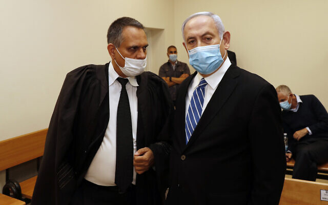 Prime Minister Benjamin Netanyahu (R) talks with attorney Micha Fettman (L) inside the court room as his corruption trial opens at the Jerusalem District Court, May 24, 2020 (Ronen Zvulun/ Pool Photo via AP)
