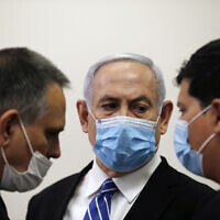Prime Minister Benjamin Netanyahu (C) talks with attorneys Micha Fettman (L) and Amit Hadad (R) inside the court room as his corruption trial opens at the Jerusalem District Court, May 24, 2020 (Ronen Zvulun/ Pool Photo via AP)