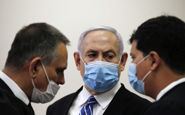 Prime Minister Benjamin Netanyahu (C) talks with attorneys Micha Fettman (L) and Amit Hadad (R) inside the courtroom as his corruption trial opens at the Jerusalem District Court, May 24, 2020 (Ronen Zvulun/ Pool Photo via AP)