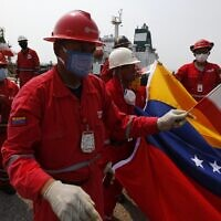 A Venezuelan oil worker holding a small Iranian flag attends a ceremony for the arrival of Iranian oil tanker Fortune at the El Palito refinery near Puerto Cabello, Venezuela on May 25, 2020. (AP Photo/Ernesto Vargas)