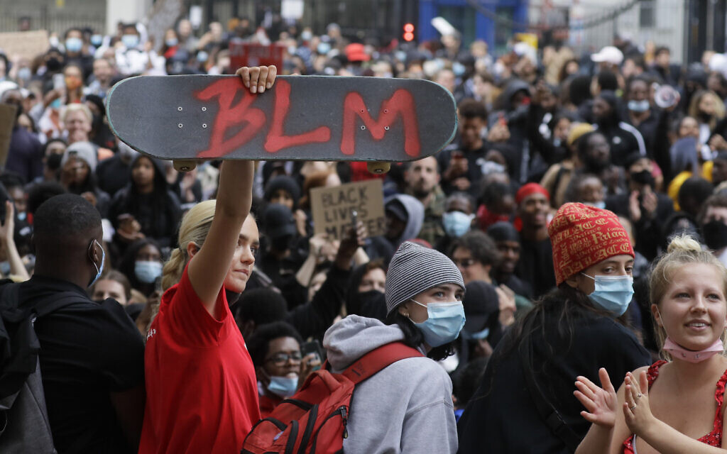 A protester holds up a skateboard with the Black Lives Matter initials in London, Wednesday, June 3, 2020, during a demonstration over the death of George Floyd, a black man who died after being restrained by police in Minneapolis, Minnesota. (AP Photo/Kirsty Wigglesworth)