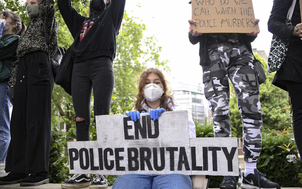 A girl holds a placard during a Black Lives Matter rally in Parliament Square in London, Saturday, June 6, 2020, as people protest against the killing of George Floyd by police officers in Minneapolis, Minnesota. (AP Photo/Alberto Pezzali)