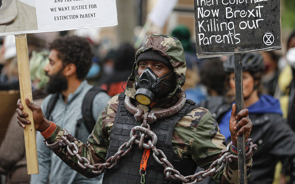 A demonstrator take part in a Black Lives Matter rally in Parliament Square in London, Saturday, June 6, 2020, as people protest against the killing of George Floyd by police officers in Minneapolis, Minnesota. (AP Photo/Frank Augstein)