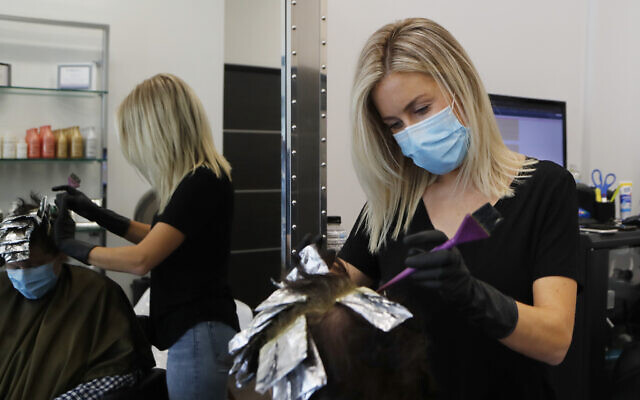 Illustrative: A hair stylist works on a customer, Monday, June 15, 2020, in Royal Oak, Mich.  (AP Photo/Carlos Osorio)