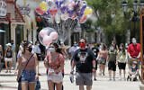 Guests required to wear masks because of the coronavirus pandemic stroll through the Disney Springs shopping, dining and entertainment complex, on June 16, 2020, in Lake Buena Vista, Florida. (AP Photo/John Raoux)