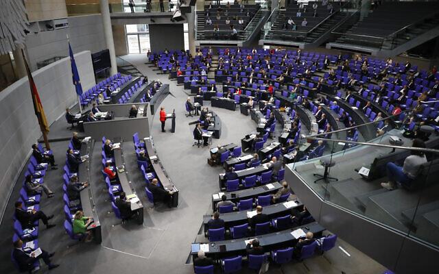 Illustrative: German Chancellor Angela Merkel, center in red, addresses the Bundestag ahead of a EU summit in Berlin, Germany, June 18, 2020. (AP Photo/Markus Schreiber)