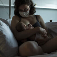 Illustrative: Marie L'Hoest, wearing a face mask to protect against the spread of coronavirus, breastfeeds her newborn daughter Anouk at the MontLegia CHC hospital in Liege, Belgium, Friday, June 26, 2020.(AP Photo/Francisco Seco)