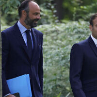 French President Emmanuel Macron, right, and French Prime Minister Edouard Philippe arrive for a meeting with members of the Citizens' Convention on Climate to discuss over environment proposals at the Elysee Palace in Paris on June 29, 2020. (Christian Hartmann/Pool via AP)
