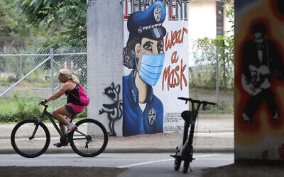 A bicyclist passes by a COVID-19 related wall painting in the Deep Ellum section of Dallas, June 30, 2020. (LM Otero/AP)