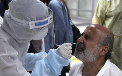 A healthcare worker takes a swab from of a passenger who arrived at the Rafik Hariri International Airport in Beirut, Lebanon, July 1, 2020. (Bilal Hussein/AP)