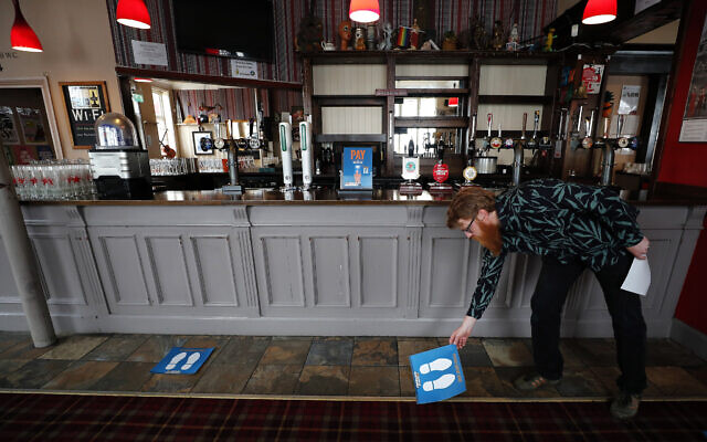 Owner Are Kjetil Kolltveit places markers for social distancing on the front of the bar at the Chandos Arms pub in London, July 1, 2020 (AP Photo/Frank Augstein)