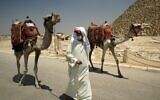A camel guide wears a surgical mask while pulling his camel at the Giza Pyramids in Giza, Egypt, July 1, 2020. (Hamada Elrasam/AP)