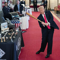 US President Donald Trump swings a baseball bat during the Spirit of America Showcase at the White House, July 2, 2020, in Washington. (AP Photo/Evan Vucci)