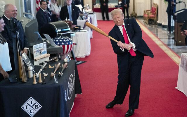 US President Donald Trump swings a baseball bat during the Spirit of America Showcase at the White House, July 2, 2020, in Washington. (AP Photo/Evan Vucci)