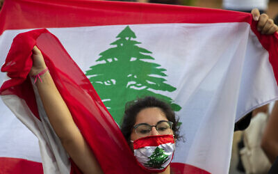 An anti-government protester shouts slogans while wearing a mask with the colors of the Lebanese flag in Beirut, Lebanon, July 2, 2020. (Hassan Ammar/AP)