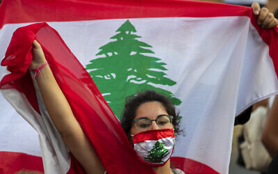 An anti-government protester shouts slogans while wearing a mask with the colors of the Lebanese flag in Beirut, Lebanon, on July 2, 2020. (Hassan Ammar/AP)
