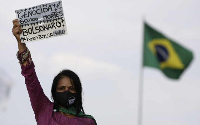 A women's movement activist holds a sign that reads in Portuguese 'Genocide 60 thousand deaths, Bolsonaro out,' during a protest against the government's inefficiency in the face of the new coronavirus pandemic and the ongoing police brutality against blacks, in front of the National Congress, in Brasilia, Brazil, July 2, 2020. (AP Photo/Eraldo Peres)