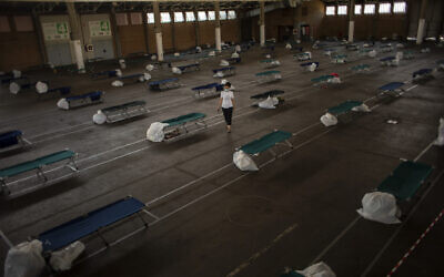A local worker walks along an exhibition center turned into a temporary seasonal workers' shelter in Lleida, Spain, on July 2, 2020  (AP Photo/Emilio Morenatti)