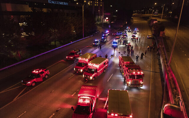 Emergency personnel work at the site where a driver sped through a protest-related closure on the Interstate 5 freeway in Seattle, authorities said, July 4, 2020 (James Anderson via AP)