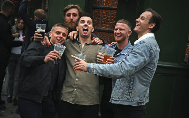 Men pose for a photo, outside a pub as it reopened, in Borough Market, as coronavirus lockdown restrictions are eased across England, in London on July 4, 2020. (Victoria Jones/PA via AP)