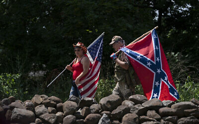 TIlustrative: People carry an American flag and a Confederate flag as they walk on a pathway at the Gettysburg National Military Park, Saturday, July 4, 2020, in Gettysburg, Pa. (AP Photo/Carolyn Kaster)
