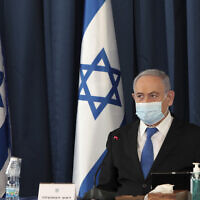 Prime Minister Benjamin Netanyahu wears a face mask to help prevent the spread of the coronavirus as he opens the weekly cabinet meeting, at the foreign ministry, in Jerusalem, July 5, 2020. (Gali Tibbon/AP)