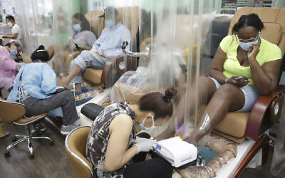 Customers sit behind plastic curtains while getting a pedicure at HT&V Nails in New York, July 6, 2020 (AP Photo/Seth Wenig)