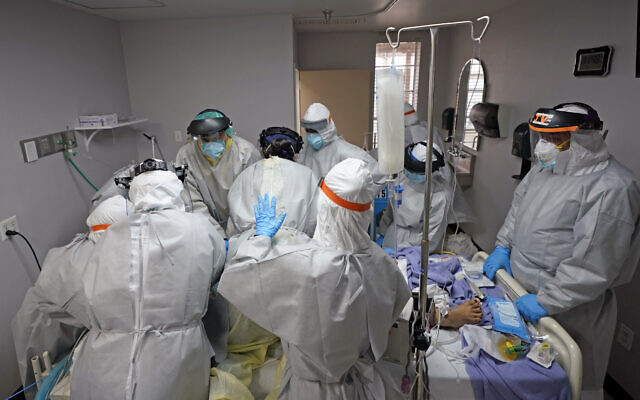 Medical personnel struggle, in vain, to save the life of a patient in the coronavirus unit at United Memorial Medical Center in Houston, Texas, July 6, 2020. (AP Photo/David J. Phillip)