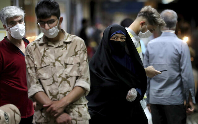 People wearing protective face masks to help prevent the spread of the coronavirus walk in a Tehran metro station on July 8, 2020. (AP Photo/Ebrahim Noroozi)