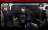 People wearing protective face masks to help prevent the spread of the coronavirus stand inside a train in Tehran, Iran, July 8, 2020. (AP Photo/Ebrahim Noroozi)