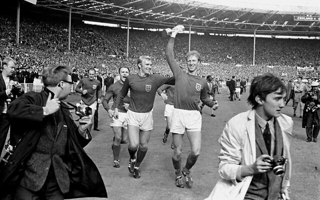 In this July 30, 1966 file photo England's Jack Charlton, right, holds the Jules Rimet trophy aloft as he parades it around Wembley with teammate Bobby Moore following their 4-2 win over West Germany (PA via AP)