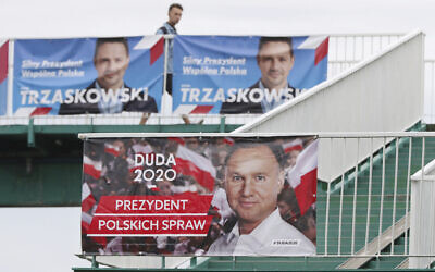 A man walks by campaign posters showing two contenders in Poland's presidential election runoff, conservative incumbent President Andrzej Duda and his rival, liberal Warsaw Mayor Rafal Trzaskowski, top, in Warsaw, Poland, July 11, 2020. (AP Photo/Czarek Sokolowski)