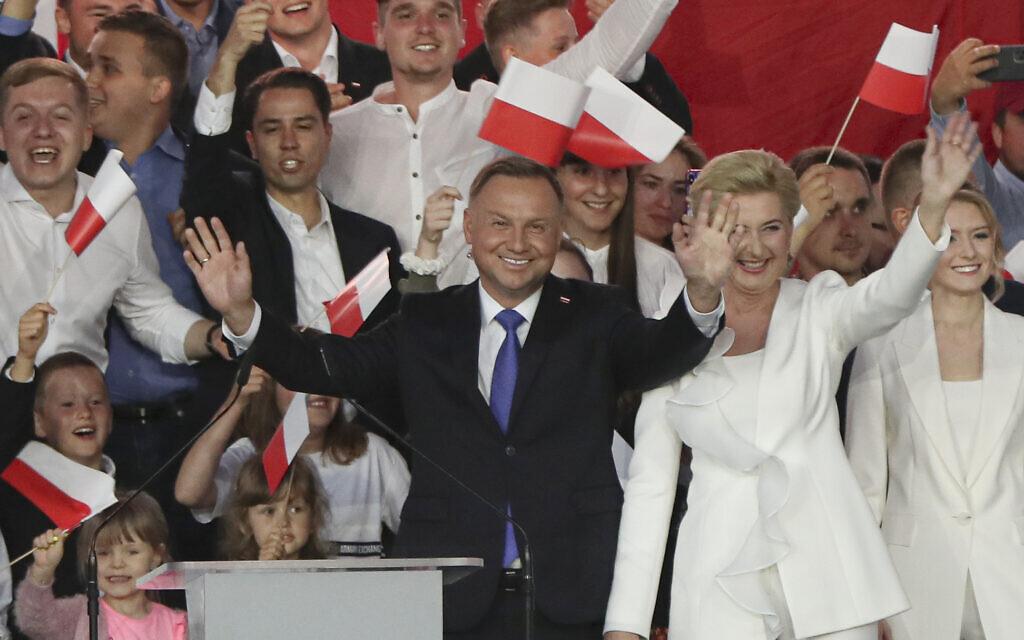 Incumbent President Andrzej Duda, left, and his wife Agata Kornhauser-Duda wave to supporters in Pultusk, Poland, July 12, 2020 (AP Photo/Czarek Sokolowski)
