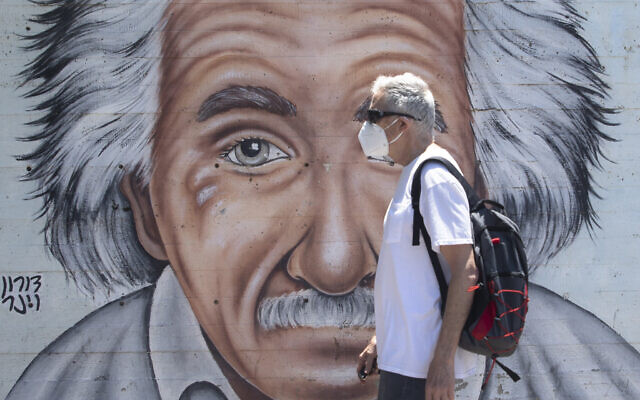 An Israeli man wearing a mask to curb the spread of the coronavirus walks past a mural showing Albert Einstein in Tel Aviv, July 15, 2020. (AP/Sebastian Scheiner)